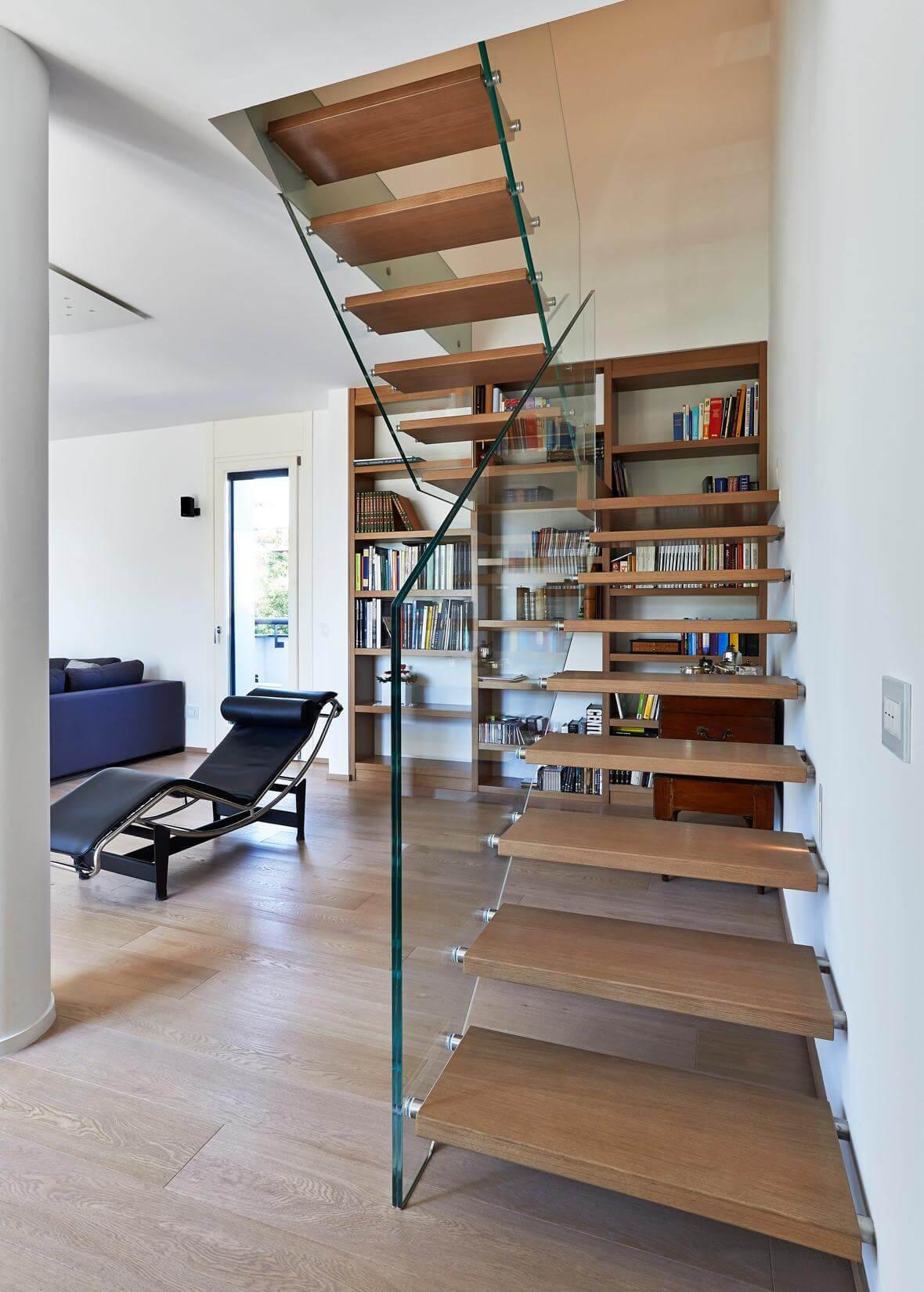 Glastragende Treppe mit Bücherregal – eine Einheit